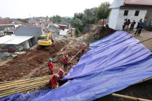 Petugas Pasang Terpal untuk Menutupi Tanah Longsor di Nerada Estate Ciputat