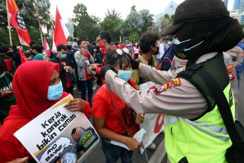 Polisi Bagikan Masker Kepada Pendemo di Surabaya