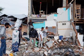 Warga Cari Barang di Reruntuhan Sisa Gempa Mamuju